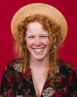 Jeune femme rousse souriant largement à la caméra