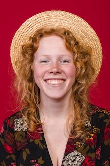 Jeune femme rousse souriante sur fond bordeaux