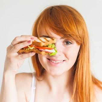 Jeune femme rousse souriante tenant un sandwich devant ses yeux