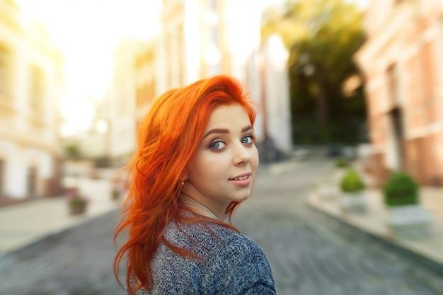 Jeune femme rousse surprise regardant la caméra par-dessus son épaule alors qu'elle se promène dans une rue urbaine déserte