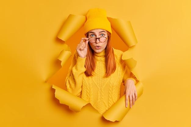 Une jeune femme rousse surprise regarde choquée à travers des lunettes impressionnée par quelque chose qui porte un chapeau et un pull se brise à travers un trou déchiré en papier jaune.