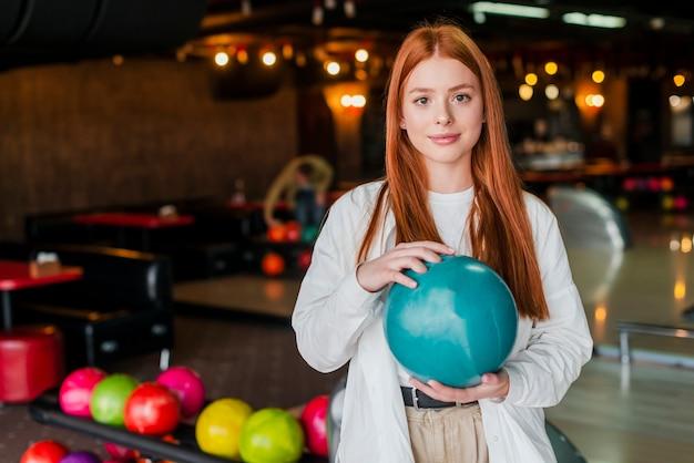 Jeune femme rousse tenant une boule de bowling turquoise
