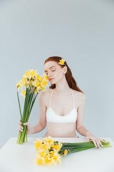 Jeune femme rousse tenant deux bouquets de narcisses