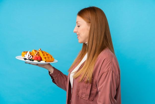 Jeune femme rousse tenant des gaufres avec une expression heureuse