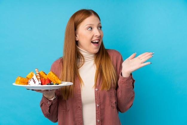 Jeune femme rousse tenant des gaufres sur un mur isolé avec une expression faciale surprise