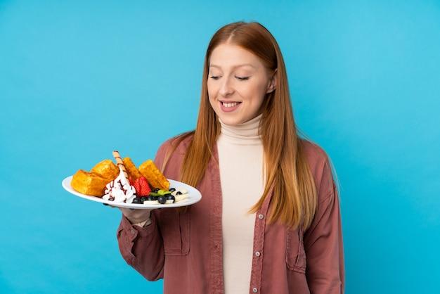 Jeune femme rousse tenant des gaufres sur un mur isolé avec une expression heureuse