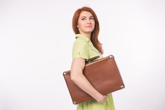 Jeune femme rousse tenant une valise rétro sur fond blanc.