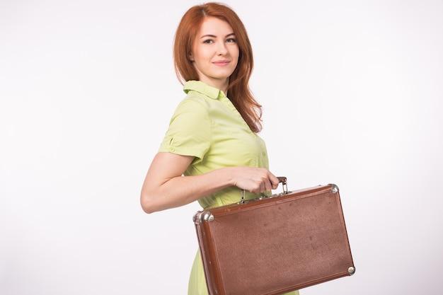 Jeune femme rousse avec valise vintage en cuir.