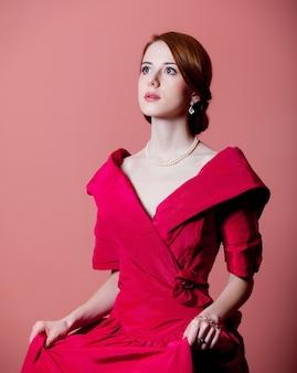 Jeune femme rousse en vêtements d'époque victorienne rouge sur rose