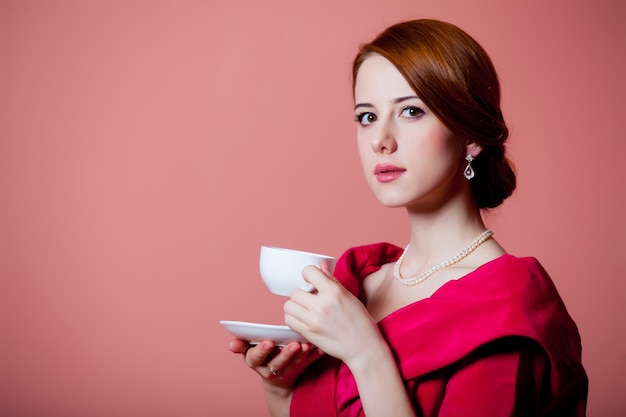 Jeune femme rousse en vêtements d'époque victorienne rouge avec tasse de thé sur rose