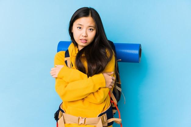 Jeune femme de routard chinois isolé qui devient froid en raison d'une basse température ou d'une maladie.