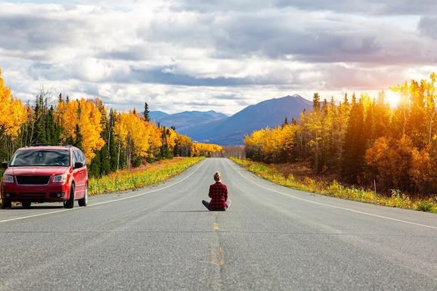 Jeune femme de routard voyageant autour du canada fille de voyageur assise seule sur la route