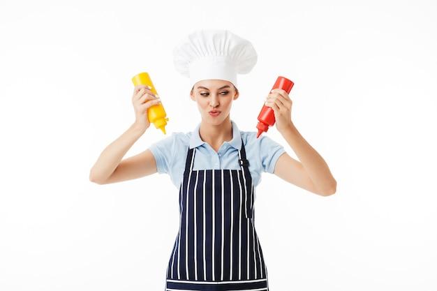Jeune femme rusée cuisinier en tablier rayé et chapeau blanc pensivement