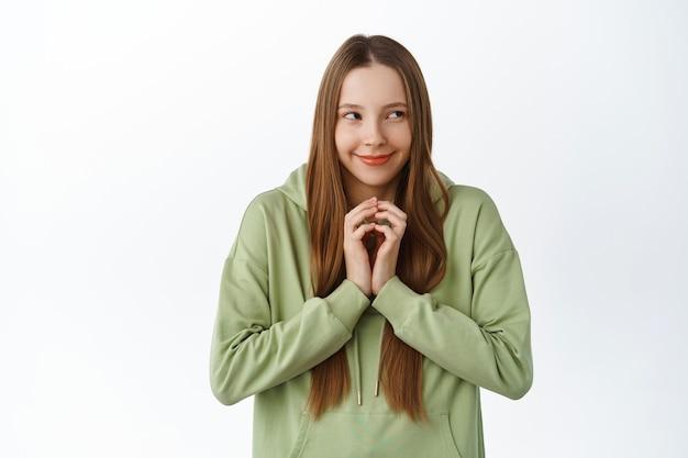 Une jeune femme rusée a un plan intéressant, des doigts de clocher comme intrigants et regardant de côté, réfléchissez à un schéma, debout sur un mur blanc