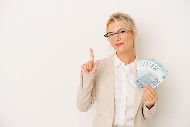Jeune femme russe d'affaires tenant des billets isolés sur fond blanc montrant le numéro un avec le doigt.