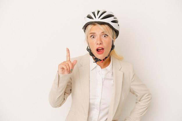 Jeune femme russe d'affaires tenant un casque de vélo isolé sur fond blanc ayant une idée, concept d'inspiration.