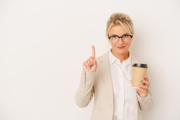 Jeune femme russe d'affaires tenant du café à emporter isolé sur fond blanc montrant le numéro un avec le doigt.