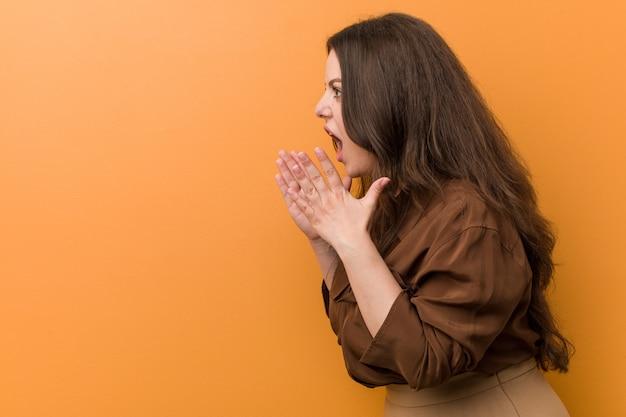 Une jeune femme russe bien roulée crie fort, garde les yeux ouverts et les mains tendues.