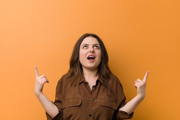 Jeune femme russe bien roulée indique avec les deux doigts antérieurs un espace vide.