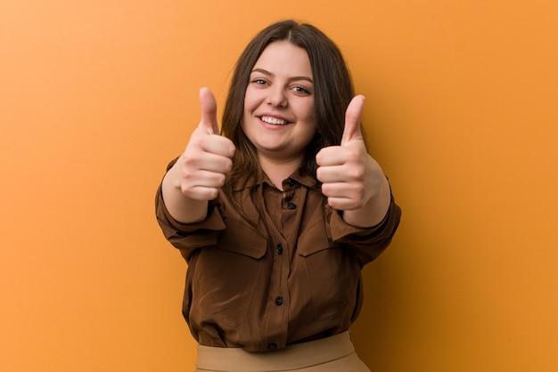 Jeune femme russe bien roulée avec le pouce levé, acclamations, soutien et respect.