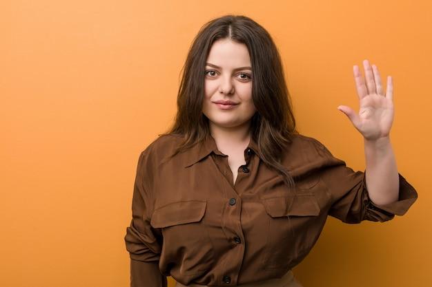 Jeune femme russe bien roulée souriant joyeux montrant le numéro cinq avec les doigts.