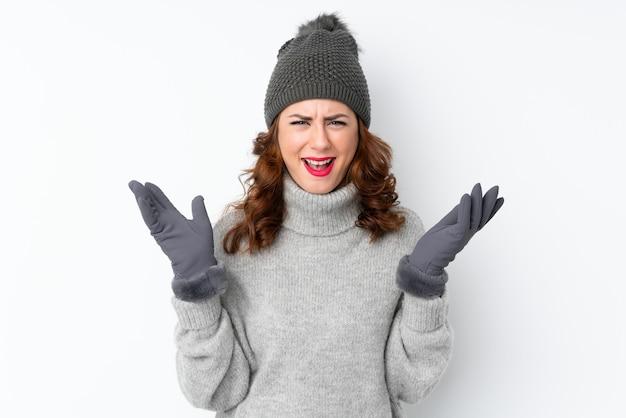 Jeune femme russe avec un chapeau d'hiver sur fond blanc isolé malheureux et frustré par quelque chose