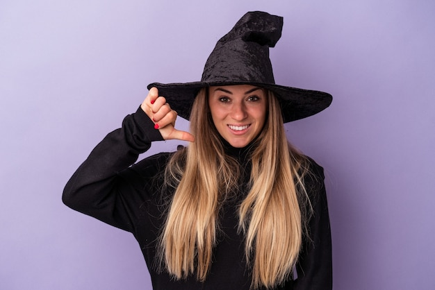 Jeune femme russe déguisée en sorcière célébrant halloween isolée sur fond violet montrant un geste d'aversion, les pouces vers le bas. notion de désaccord.