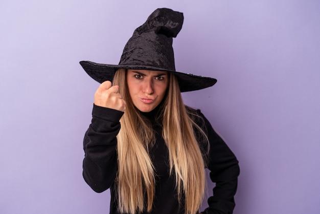 Jeune femme russe déguisée en sorcière célébrant halloween isolée sur fond violet montrant le poing à la caméra, expression faciale agressive.