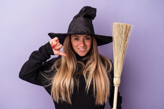 Jeune femme russe déguisée en sorcière tenant un balai isolé sur fond violet montrant un geste d'aversion, les pouces vers le bas. notion de désaccord.