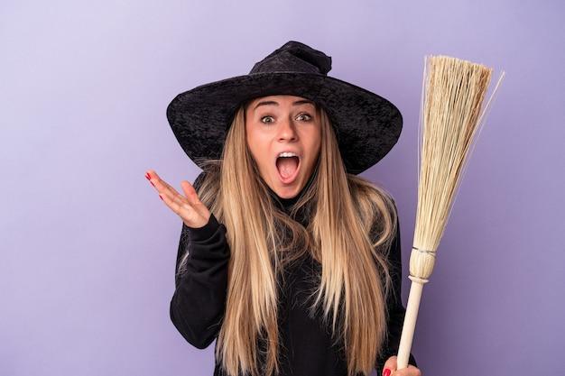 Jeune femme russe déguisée en sorcière tenant un balai isolé sur fond violet surprise et choquée.
