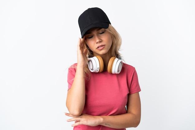 Jeune femme russe écoute de la musique isolée sur blanc avec des maux de tête
