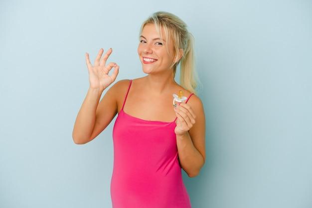 Jeune femme russe enceinte tenant une tétine isolée sur fond bleu joyeux et confiant montrant un geste ok.