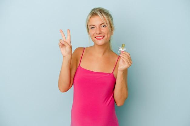 Jeune femme russe enceinte tenant une tétine isolée sur fond bleu montrant le numéro deux avec les doigts.