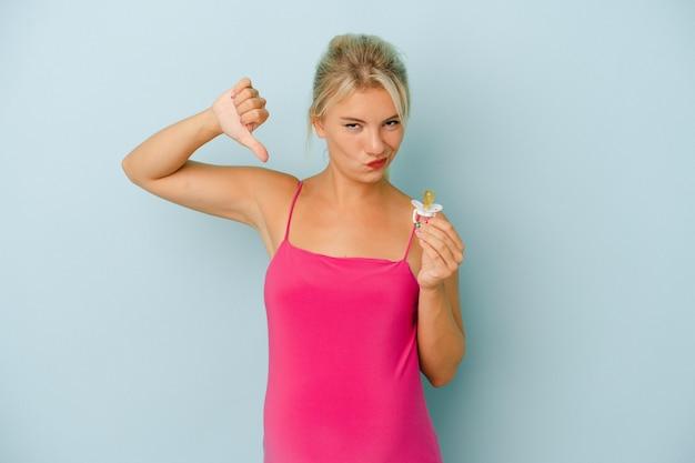Jeune femme russe enceinte tenant une tétine isolée sur fond bleu se sent fière et confiante, exemple à suivre.