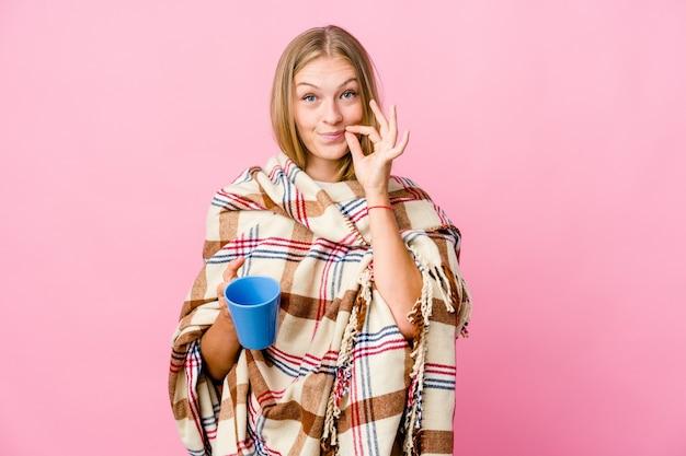 Jeune femme russe enveloppée dans une couverture de boire du café avec les doigts sur les lèvres en gardant un secret