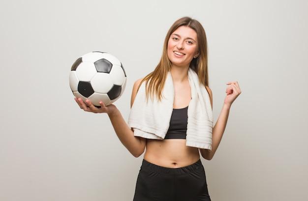 Jeune femme russe de fitness sourit, pointant la bouche. tenant un ballon de soccer.