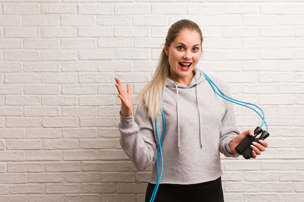 Jeune femme russe de fitness tenant une corde à sauter contre un mur de briques