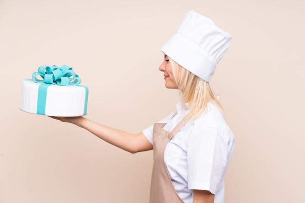 Jeune femme russe avec un gros gâteau sur un mur isolé avec une expression heureuse
