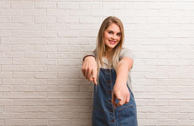 Jeune femme russe hipster joyeuse et souriante pointant vers l'avant