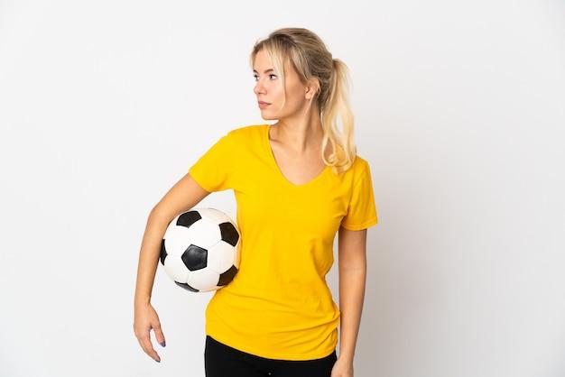 Jeune femme russe isolée sur blanc avec ballon de foot