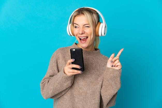 Jeune femme russe isolée sur bleu écoute de la musique avec un mobile et le chant