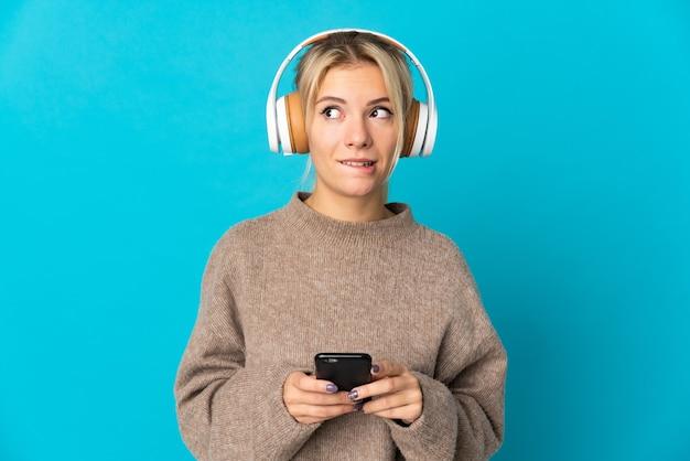 Jeune femme russe isolée sur bleu écoute de la musique avec un mobile et de la pensée