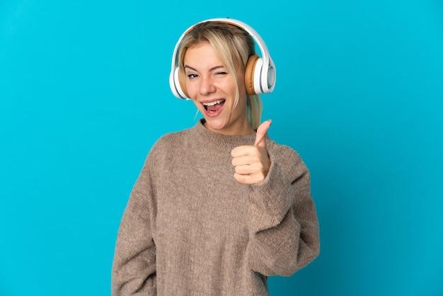 Jeune femme russe isolée sur bleu écoute de la musique et avec le pouce vers le haut