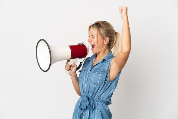 Jeune femme russe isolée sur fond blanc criant à travers un mégaphone pour annoncer quelque chose en position latérale