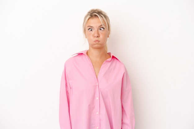Jeune femme russe isolée sur fond blanc souffle les joues, a une expression fatiguée. concept d'expression faciale.