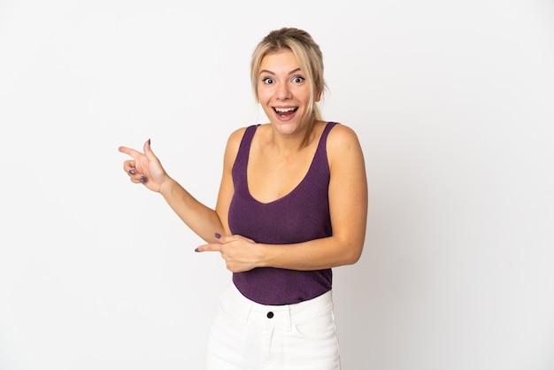 Jeune femme russe isolée sur fond blanc surpris et côté pointant