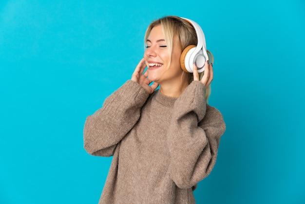 Jeune femme russe isolée sur fond bleu à l'écoute de la musique et du chant
