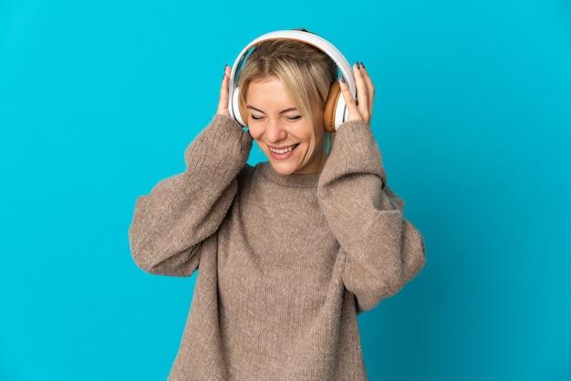 Jeune femme russe isolée sur fond bleu à l'écoute de la musique