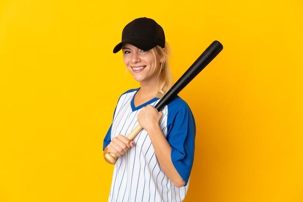 Jeune femme russe isolée sur fond jaune jouant au baseball