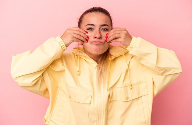 Jeune femme russe isolée sur fond rose doutant entre deux options.